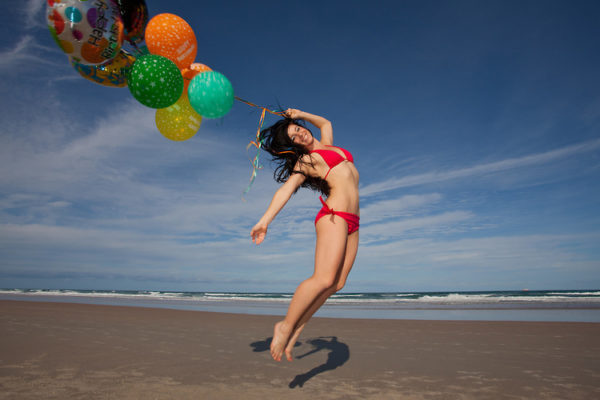 Young Woman at beach celebrating her birthday with Balloons on a Beach